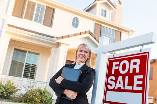 Female Real Estate Agent in Front of For Sale Sign and Beautiful House.