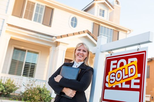 Female Real Estate Agent in Front of Sold For Sale Sign and Beautiful House.