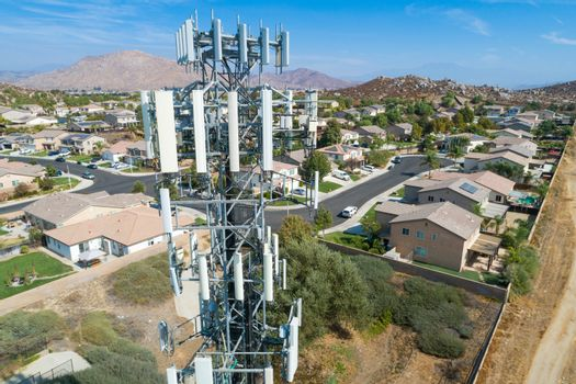 Close-up Aerial of Cellular Wireless Mobile Data Tower with Neighborhood Surrounding.