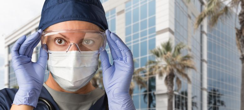 Female Doctor or Nurse Wearing Scrubs, Protective Face Mask and Goggles.