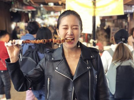 Young woman eating Steamed Octopus Legs at  at Myeong-dong street food, Seoul, South Korea