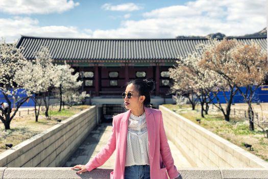 Young beautiful woman visiting the beautiful Gyeongbokgung Palace, Seoul, South Korea on a sunny day