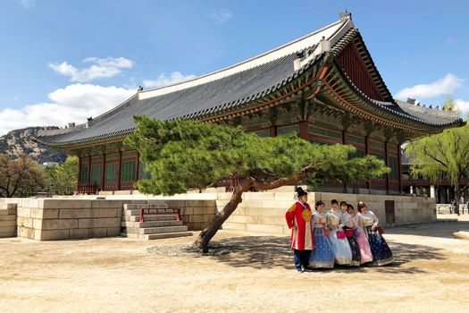 28 MARCH : A group of tourist wearing traditional korean clothing, hanbok, and taking group photo at Gyeongbokgung Palace at 28 March 2018