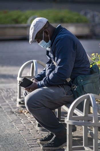 terni,italy november 11 2020:black man with medical mask sitting on a planter