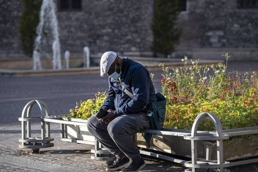 terni,italy november 11 2020:black man with medical mask sitting on a planter