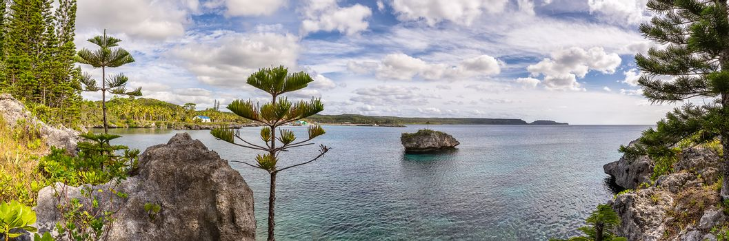 Amazing panoramic shot of Island of Mare in New Caledonia. Lone massive cliff in the water next to the island. Trees and rocks in the foreground. Blue cloudy sky as a background.