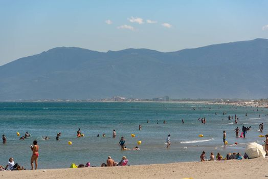 Canet en Roussillon, France: June 21, 2020: People in the beach. Sunny day in the tourist town of Canet en Roussillion in France on the Mediterranean Sea.