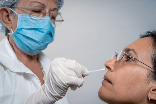 Elderly nurse, with a nasal swab taking samples from a younger woman. The nurse is wearing a face mask and gloves on her hands