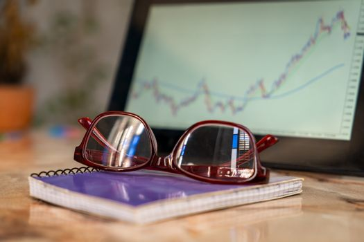 Close-up photo of an glasses on a notebook. There is a tablet screen out of focus with a graphic, in the background