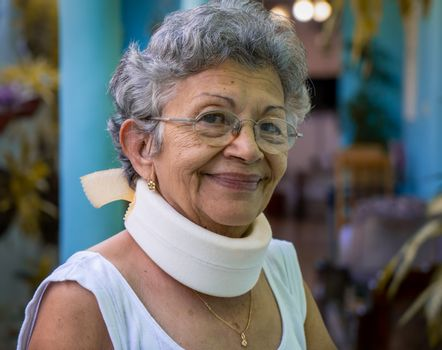 Smiling elderly woman wearing homemade looking cervical immobilizer collar