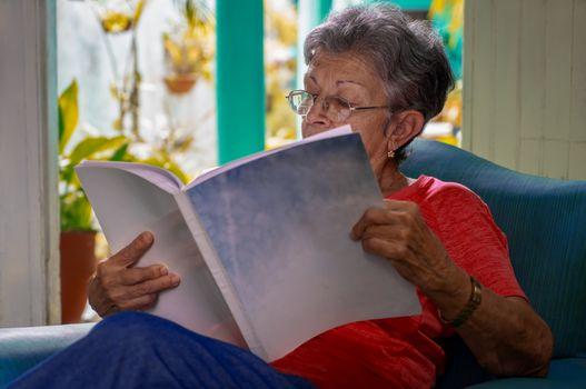 Senior woman wearing eyeglasses sitting reading a book