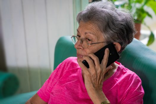 Senior woman with eyeglasses sitting, using a cell phone