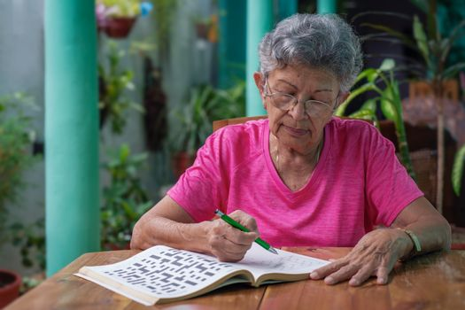 Senior woman with glasses sitting at a table, filling in a sudoku puzzle