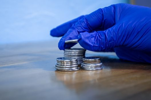 Protected hand with a blue glove manipulating money coins