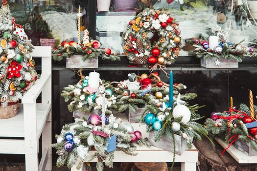 Small decorated Christmas trees decorated are on sale in flower shop window. Wreaths and decoration for New Year celebration. Winter holiday spirit.