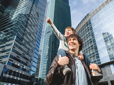 Little boy sits on father's shoulders and points on skyscraper. Dad and son looks on glass walls of buildings. Future and modern technologies, life balance and family life in well keeps districts.