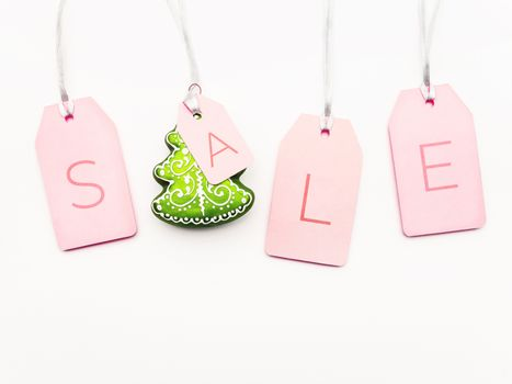 Four pink tags with word SALE and decorative Christmas tree on white background. Glamorous labels on silver threads. New Year symbol of sale and shopping. Top view, flat lay.