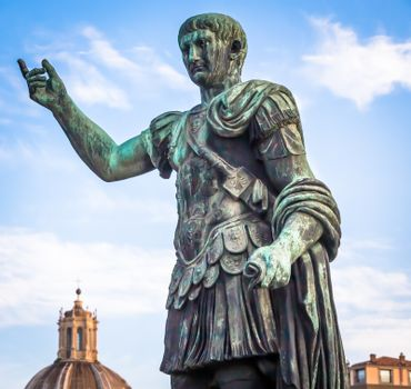 ITALY, ROME - CIRCA AUGUST 2020: Statue of Caesar Emperor, made of bronze. Natural sunrise light. Ancient  role model of Leadeship and Authority .