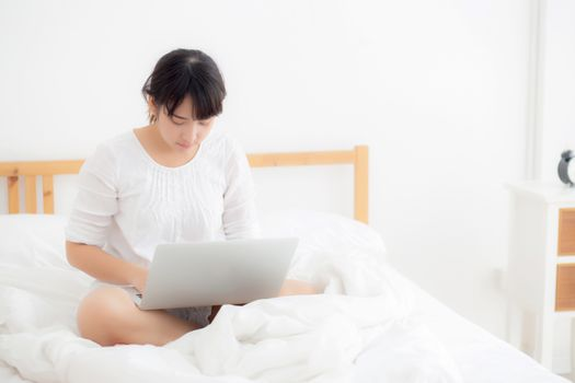 Portrait of beautiful asian young woman sitting on bed using laptop computer at bedroom for leisure and relax, freelance with girl working notebook, communication and lifestyle concept.