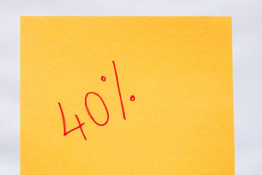 40% handwriting text close up isolated on orange paper with copy