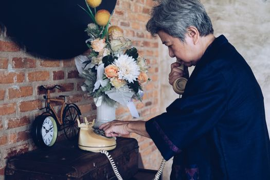 old asian elderly senior elder woman dialing telephone number