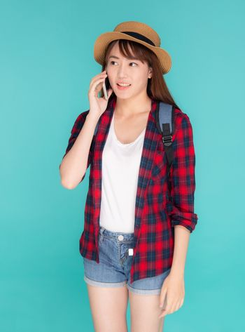 Beautiful young asian woman talking smart mobile phone in vacation isolated on blue background, asia girl conversation on smartphone in travel summer trip, journey and communication  concept.