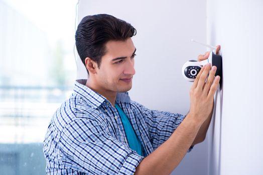 Man installing surveillance CCTV cameras at home