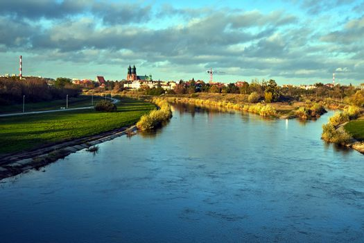 Urban landscape with river Warta and the cathedral towers in the fall