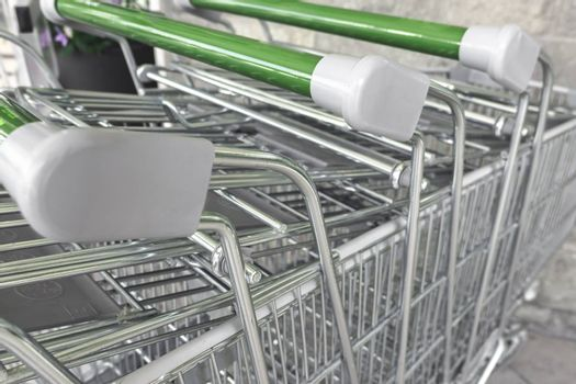 Details of Rows of shopping carts outside waiting to be used.