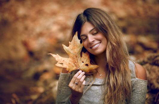 Portrait of a Beautiful Girl Enjoying  Autumn Forest. Holding in Hand Dry Maple Leaf. Happy Positive Face. Beauty of Fall Season