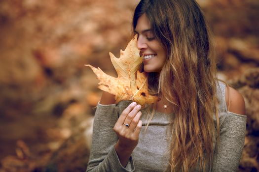 Portrait of a Pretty Woman Enjoying  Autumn Nature. Holding in Hands Dry Maple Leaf and Closing Eyes of Pleasure. Having Fun in the Fall Forest.