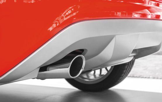 Exhaust pipe of a red car. Ecology concept, low emission, low environmental impact.