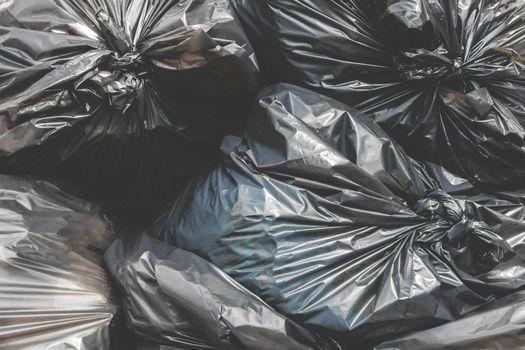 Garbage pile black plastic bags and trash bag waste pollution. Stack of black garbage bags.Black plastic bags for packaging waste.