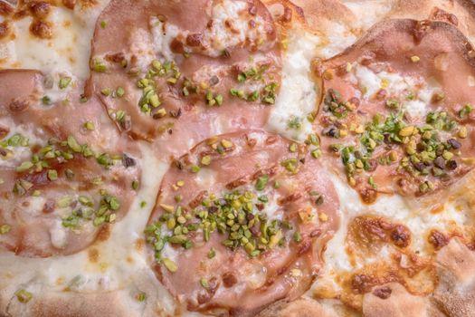 Gourmet pizza with mortadella, pistachio grains and mozzarella.