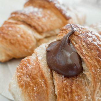 Homemade Chocolate Croissants. Fresh italian croissants filled by chocolate cream. Close-up.