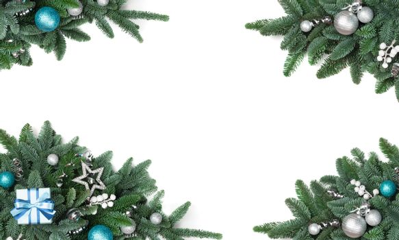 Christmas design element of noble fir tree branches and silver baubles isolated on white background