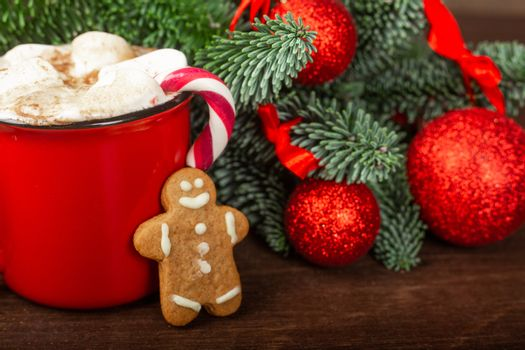 Cocoa hot chocolate in red mug with marshmallows candy cane gingerbread cookie man fir tree branches and red baubles on dark wooden background