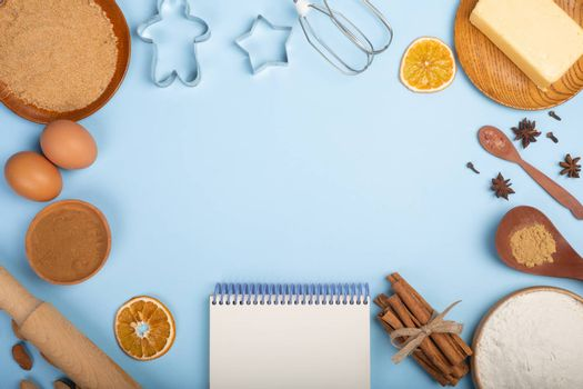 Christmas gingerbread cookies cooking background flat lay top view template with copy space for text. Baking utensils, spices and food ingredients on blue background