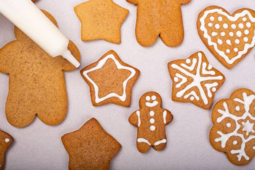 Close up of decorating the gingerbread cookies with white glaze, Merry Christmas concept