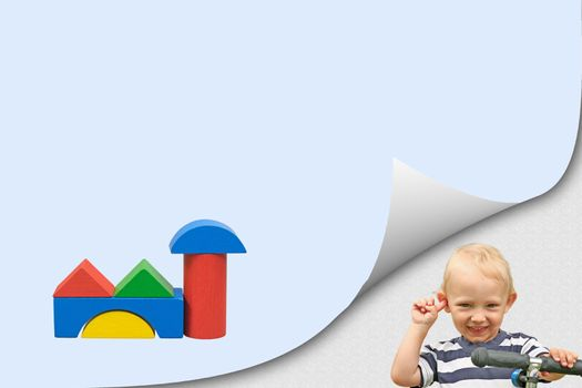 Smiling blond boy in bent corner of the page and colorful building  of wooden cubes on blue blank paper ready for your use.
