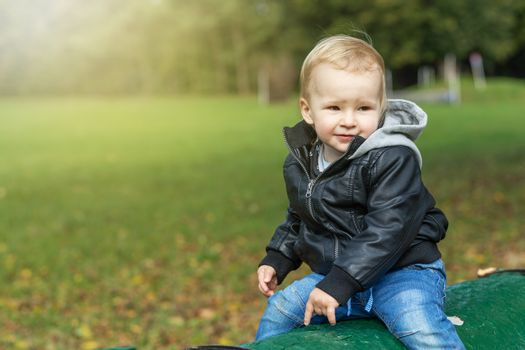 Little boy dressed  in a leather jacket is posing in autumn park