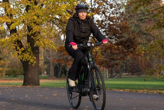 11/14/2020. Park Stromovka. Prague. Czech Republic. A woman is riding his bike at the park on a winter day.