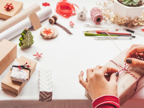 Table with Christmas decorations. Woman draws New Year symbols on craft paper and wraps presents. Flat lay with copy space.