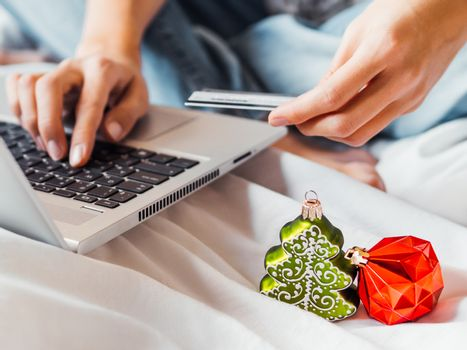 Woman using laptop to pay for online order by credit card. Decorative Christmas tree and New Year red ball in her hand. Online shopping before winter holidays.