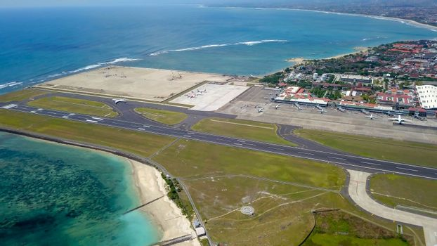 Commercial aircraft taxi on the runway at Denpasar Airport in Bali, Indonesia. Drone view of a big jet preparing to take off. Jet airplane turns to runway. Passenger jet prepares for departure
