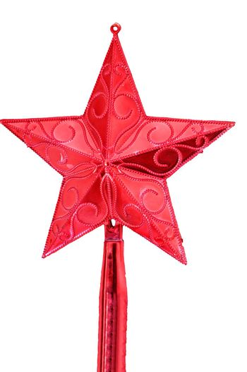 Shining red star set high up on white christmas tree. No people