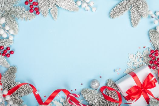 Frosted fir tree twigs and Christmas decorative bauble balls and gift with red ribbon on blue background with copy space for text template flat lay top view design