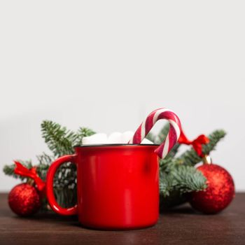 Cocoa in red mug with marshmallows candy cane fir tree branches and red baubles on wooden background with gray copy space for text