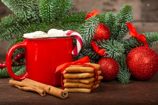 Cocoa hot chocolate in red mug with marshmallows candy cane gingerbread cookies fir tree branches and red baubles on dark wooden background