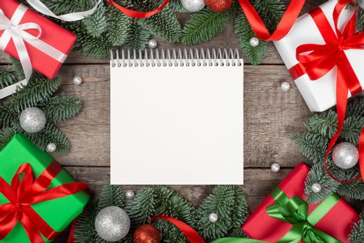 Christmas or New Year background composition made of Xmas decorations and fir tree branches and gifts with copy space for text on note pad